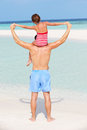 Rear view of father carrying daughter on beach holiday having fun Stock Images