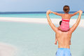 Rear view of father carrying daughter on beach holiday having fun Royalty Free Stock Photo