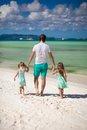 Rear view of father and his two cute daughters walking on white sand beach this image has attached release Royalty Free Stock Photography