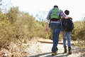 Rear view of father and son hiking in countryside with arm around Stock Image