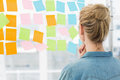 Rear view of a female artist looking at colorful sticky notes the office Stock Image