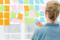 Rear view of a female artist looking at colorful sticky notes the office Royalty Free Stock Photos