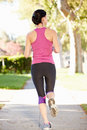 Rear view of female runner exercising on suburban street running away from camera Stock Images