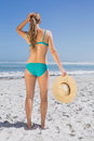 Rear view of fit woman in bikini on beach holding sunhat a sunny day Royalty Free Stock Photo