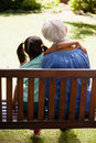 Rear view of girl with arm around grandmother sitting on wooden bench Royalty Free Stock Photo