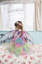 Rear view of girl in fairy costume sitting on bed a young looking through window Stock Image