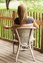 Rear view of girl sitting on veranda Stock Image
