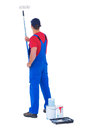 Rear view of handyman painting with roller on white background Royalty Free Stock Photo
