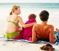 Rear view of a happy family sitting at the beach Stock Images