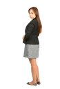 Rear view head turned serious businesswoman full of asian in black business jacket gray dress looking back over her shoulder at Stock Photo