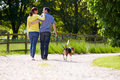 Rear view of hispanic couple walking dog in countryside Stock Images