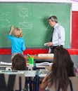 Rear view of little boy writing on board in while teacher looking at him classroom Royalty Free Stock Photo