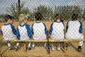 Rear view little league baseball team sitting on bench Royalty Free Stock Photo