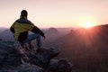 Rear view of male hiker in yellow black jacket sitting on rocky cliff while enjoying daybreak above valley the peak a mountains Royalty Free Stock Images