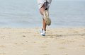 Rear view male jogger at the beach low angle Stock Photos