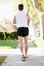 Rear view of male runner exercising on suburban street running away from camera Royalty Free Stock Image
