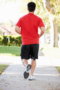 Rear view of male runner exercising on suburban street running away from camera Stock Image