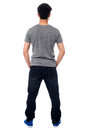 Rear view of a man in casuals full length shot young casual facing the wall studio Royalty Free Stock Photo
