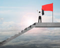Rear view man cheering on stairs top with red flag Royalty Free Stock Photo