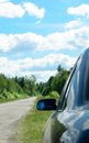Rear view mirror of the car standing on a roadside lateral forest road Stock Photos