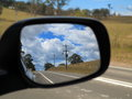 Rear view mirror reflecting landscape the australian countryside reflected in an exterior at left hand traffic Royalty Free Stock Photography