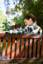 Rear view of mother and daughter sitting with arm around on wooden bench Royalty Free Stock Photo