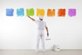 Rear view of painter man pointing with finger the colors on wall Royalty Free Stock Photo