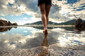 Rear view photo of beautiful female legs walking on water surfac Royalty Free Stock Photo