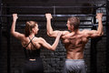 Rear view photo of couple of man and woman in the sportwear making exercise on a horizontal bar against brick wall. Royalty Free Stock Photo