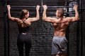 Rear view photo of muscular man and woman doing exercises on horizontal bar against brick wall at the cross fit gym.