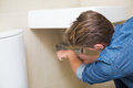 Rear view of plumber repairing washbasin drain a in bathroom Stock Photography