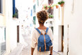 Rear view portrait of african american woman walking on street with bag Royalty Free Stock Photo