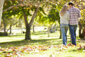 Rear View Of Romantic Couple Walking Through Autumn Woodland Royalty Free Stock Photo