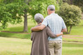 Rear view of senior couple with arms around at park a men and women standing the Stock Images