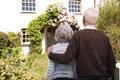 Rear view of senior couple outside pretty cottage standing Stock Photo
