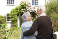 Rear view of senior couple outside pretty cottage standing Stock Images