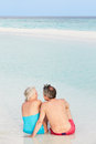 Rear view of senior couple sitting on beautiful beach relaxing Royalty Free Stock Photos