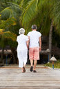 Rear view of senior couple walking on wooden jetty away from camera Stock Photo
