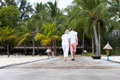 Rear view of senior couple walking on wooden jetty away from camera Royalty Free Stock Images