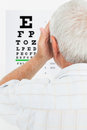 Rear view of a senior man looking at eye chart Royalty Free Stock Photo