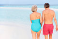 Rear view of senior romantic couple walking in tropical sea holding hands Stock Photos