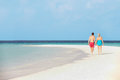 Rear view of senior romantic couple walking in tropical sea holding hands Royalty Free Stock Photography