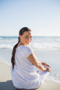 Rear view of smiling woman on the beach looking over shoulder at a sunny day camera Royalty Free Stock Photography