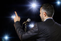 Rear view of a speaker speaking at the microphone male public pointing in spotlights symbol leadership and international Stock Photos