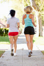 Rear view of two female runners on suburban street running away from camera Stock Image