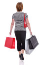 Rear view of a woman carrying shopping bags isolated smartly dressed on white background Stock Photos
