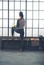 Rear view of woman looking out window holding water in loft gym Royalty Free Stock Photo