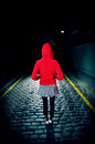 Rear view of woman in red hood on street at night full length a jacket standing cobbled Stock Images
