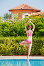 Rear view of woman that stands in tree pose at poolside young Royalty Free Stock Images