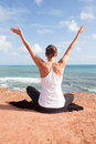 Rear view of yoga woman with arms up watching the sea while making Royalty Free Stock Photography